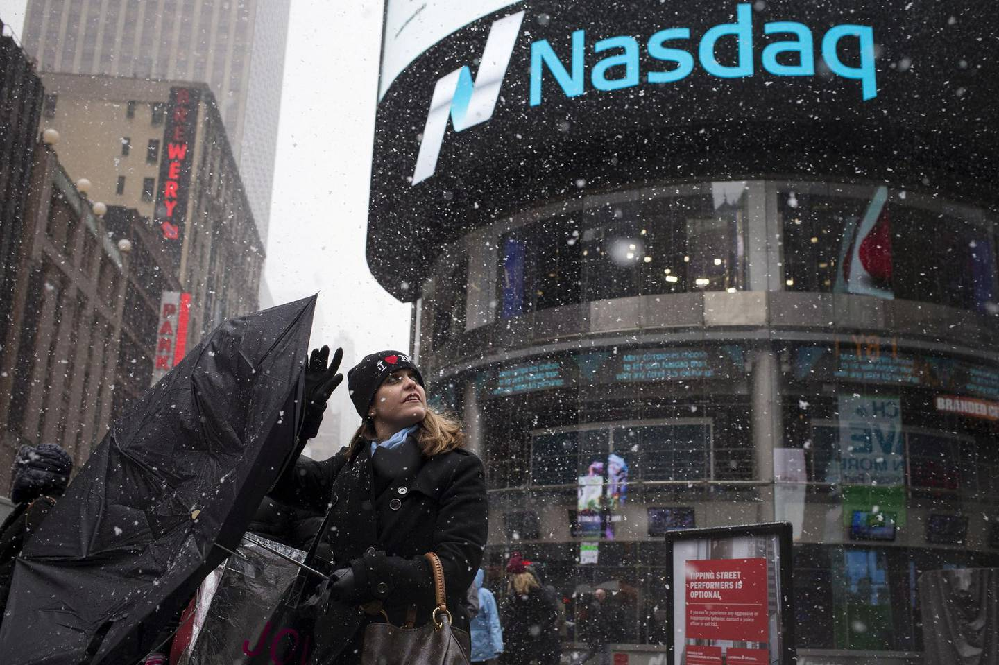 FILE PHOTO: A woman's umbrella turns inside out as she walks past the Nasdaq MarketSite during a snow storm in Times Square, New York, March 20, 2015.   REUTERS/Adrees Latif/File Photo