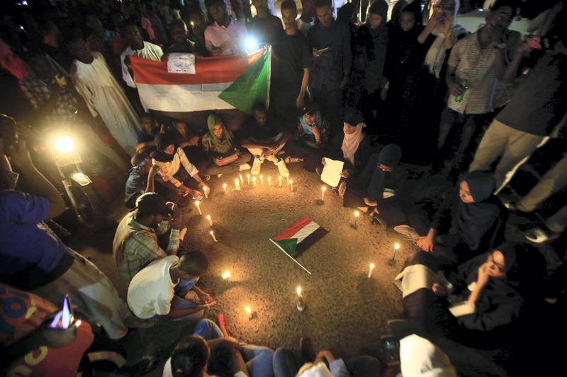 Sudanese protesters take part in a vigil in the capital Khartoum to mourn dozens of demonstrators killed last month in a brutal raid on a Khartoum sit-in, on July 13, 2019. - Crowds of protesters were violently dispersed by men in military fatigues in a pre-dawn raid on a protest site outside army headquarters on June 3. (Photo by ASHRAF SHAZLY / AFP)