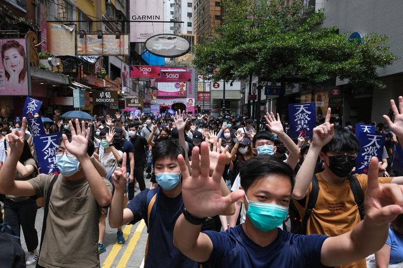 """Demonstrators gesture the """"Fivedemands, not one less"""" protest motto during a protest against a planned national security law in the Causeway Bay district in Hong Kong, China, on Sunday, May 24, 2020. Hong Kong police deployed a water cannon and fired tear gas as violence returned to the city's streets with hundreds of protesters marching against China's plans to impose a sweeping national security law. Photographer: Roy Liu/Bloomberg"""