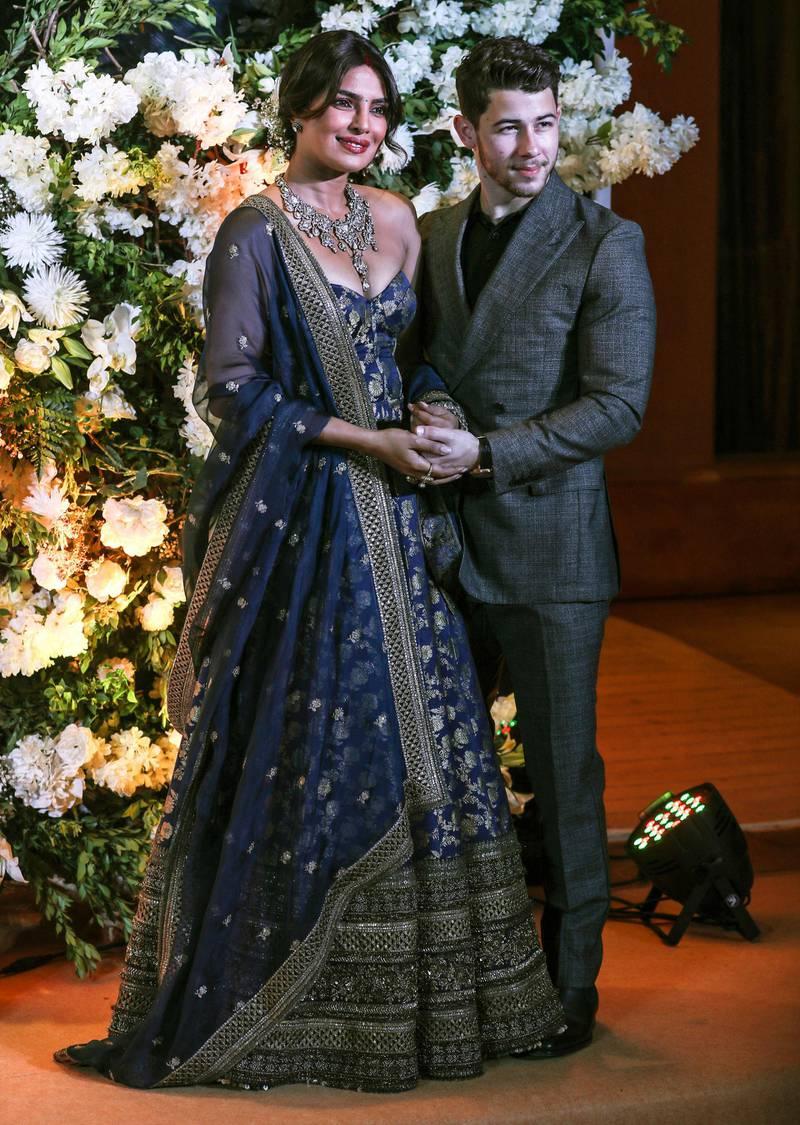 epa07240382 Newlyweds, Bollywood actress Priyanka Chopra (L) and US musician Nick Jonas (R) pose for photographs during a reception in Mumbai, India, 19 December 2018.  EPA-EFE/DIVYAKANT SOLANKI