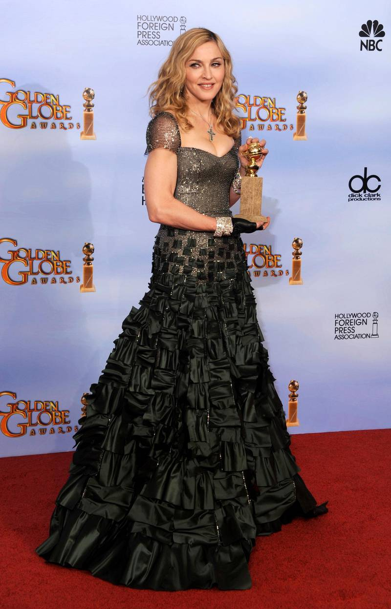 epa03061565 US singer Madonna poses with her Golden Globe award for Best Original Song in a Motion Picture for 'Masterpiece' in the Press Room at the 69th Golden Globe Awards held at the Beverly Hilton Hotel in Beverly Hills, Los Angeles, California, USA, 15 January 2012.  EPA/PAUL BUCK