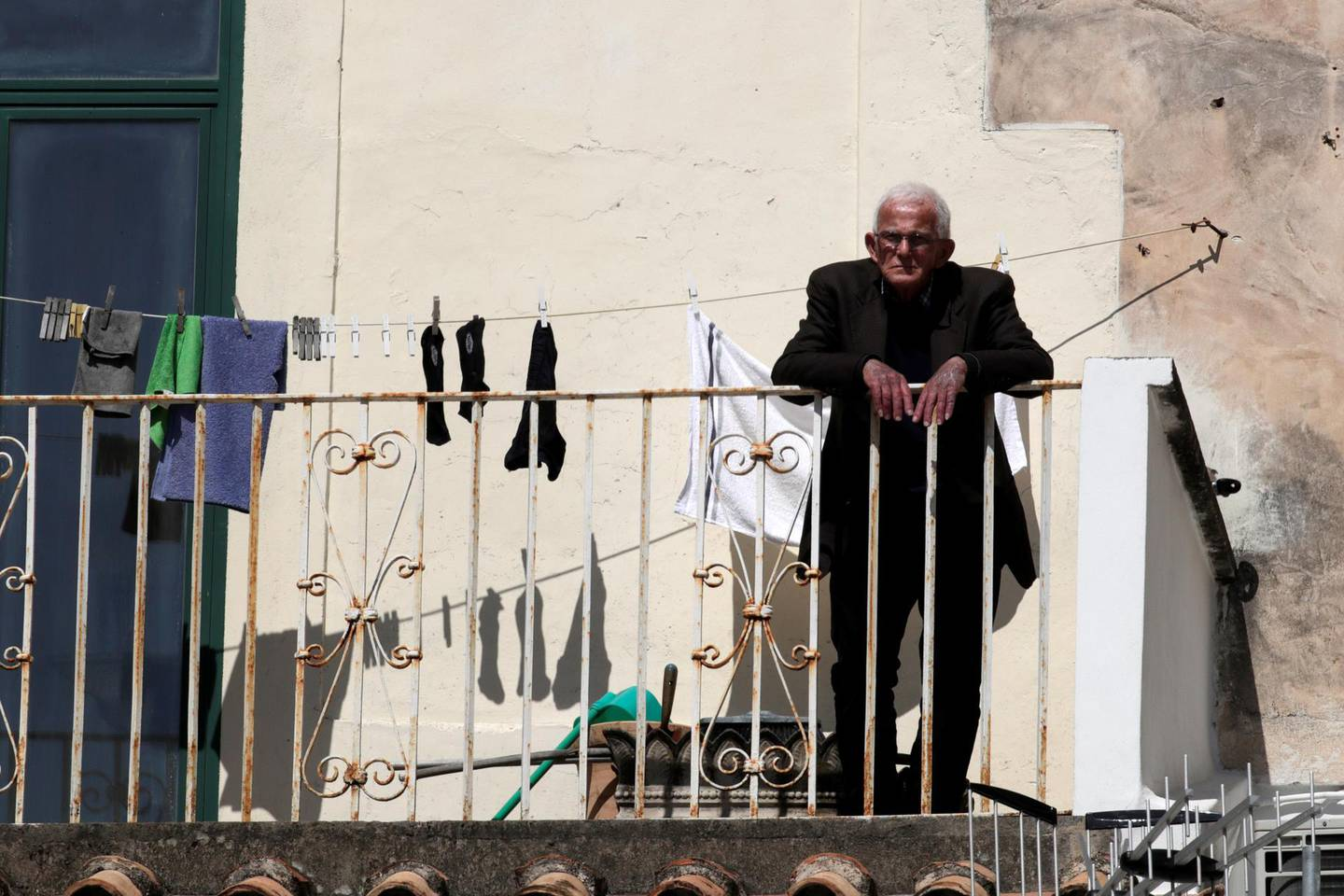 A man is seen on a balcony as Italy remains under a nationwide lockdown in a government decree that orders Italians to stay at home, in Amalfi, Italy, March 19, 2020. REUTERS/Ciro De Luca