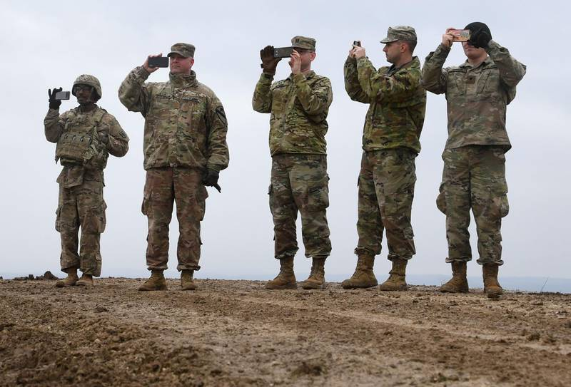 (FILES) In this file photo US soldiers take pictures with their cell phones during an artillery live fire event by the US Army Europe's 41st Field Artillery Brigade at the military training area in Grafenwoehr, southern Germany, on March 4, 2020.  The United States will slash its military presence in Germany by 11,900 troops, relocating some to Italy and Belgium in a major shift of Washington's NATO assets, Defense Secretary Mark Esper announced on july 29, 2020. Of the 34,500 US military personnel in Germany, some 6,400 will be sent home while nearly 5,600 others will be moved to other NATO countries.  / AFP / Christof STACHE