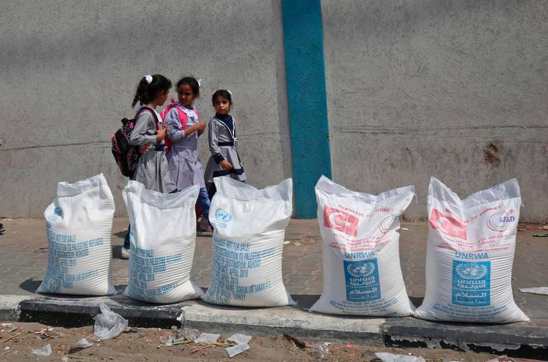 """Palestinian school girls walk past sacks of flour outside a United Nations' compound at the Rafah refugee camp in the southern Gaza Strip on September 1, 2018. - The United States announced it was halting funding for the United Nations' agency for Palestinian refugees after declaring the organisation was """"irredeemably flawed. Washington has long been the UN Relief and Works Agency's (UNRWA) largest donor but is """"no longer willing to shoulder the very disproportionate share of the burden,"""" State Department spokeswoman Heather Nauert said in a statement. (Photo by SAID KHATIB / AFP)"""