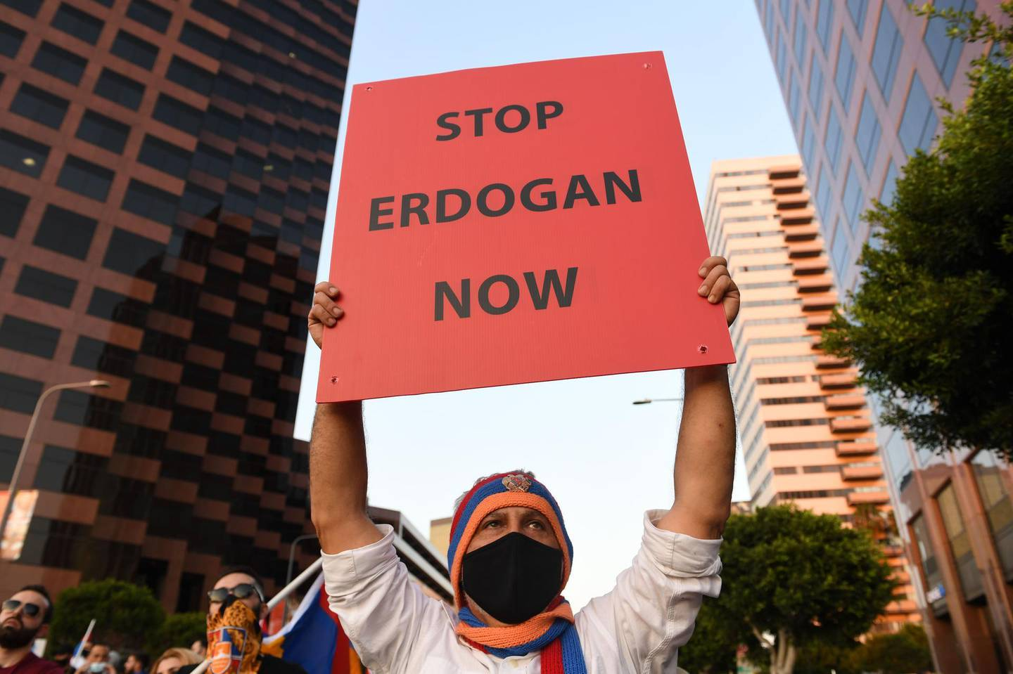 A man holds up a sign as he stands with members of the Armenian Youth Federation (AYF) during a protest outside the Azerbaijani Consulate General in Los Angeles on September 30, 2020 to protest what they call Azerbaijan's aggression against Armenia and Artsakh.  / AFP / VALERIE MACON