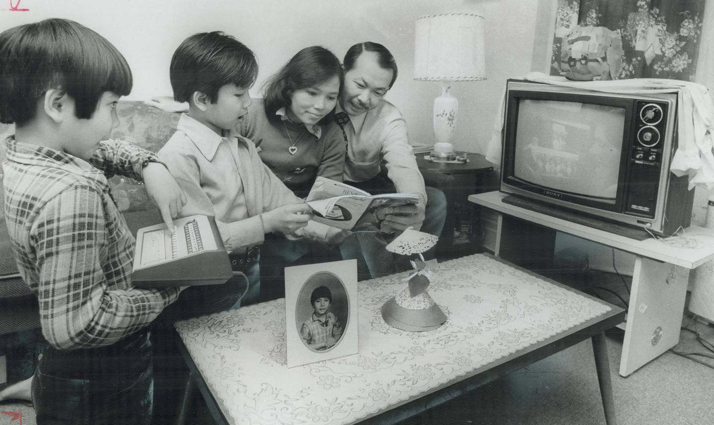 CANADA - MARCH 09: Always smiling: The Nguyen family from Viet Nam smiled in adversity when they arrived in Canada and had nothing; and they're smiling a year later now; they've made a new life for themselves. From left; Quang 7; Quy; 9; Vinh Nguyen and husband Can Khac enjoy TV at their Carlaw Ave. home. This is a great country for all of us; says Can Khae. Toronto Star readers who saw the picture of the refugees sitting in their bare living room responded magnificently with offers of everything from jobs to furniture. (Photo by Colin McConnell/Toronto Star via Getty Images)