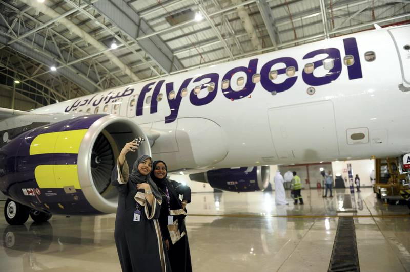 Saudi employees of the new Flydeal airlines company take a selfie during the launching ceremony held at the King Abdulaziz airport in the coastal city of Jeddah, on August 25, 2017. Saudi Arabia's new budget carrier Flyadeal said Thursday it will start flying next month, as the kingdom seeks to expand air services to boost tourism in a radical overhaul of its oil-dependent economy. / AFP PHOTO / AMER HILABI
