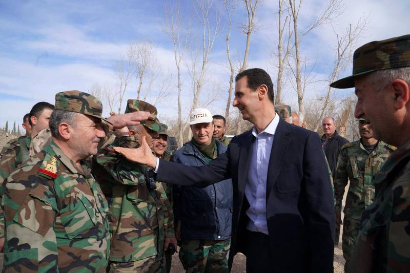 """A handout picture released by the official Facebook page of the Syrian Presidency on March 18, 2018, shows Syrian President Bashar al-Assad (C) shaking hands with government troops in Eastern Ghouta, in the leader's first trip to the former rebel enclave outside Damascus in years. - Rebels have held out in Eastern Ghouta since 2012, but a regime assault in the last month has retaken more than 80 percent of the former opposition bastion, the Britain-based Syrian Observatory for Human Rights war monitor says. (Photo by HO / Syrian Presidency Facebook page / AFP) / RESTRICTED TO EDITORIAL USE - MANDATORY CREDIT """"AFP PHOTO / HO / SYRIAN PRESIDENCY FACEBOOK PAGE"""" - NO MARKETING NO ADVERTISING CAMPAIGNS - DISTRIBUTED AS A SERVICE TO CLIENTS"""