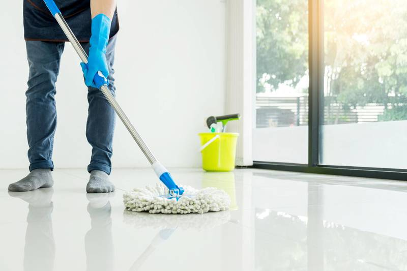 Young housekeeper cleaning floor mobbing holding mop and plastic bucket with brushes, gloves and detergents in the leaving room house floor helping his wife