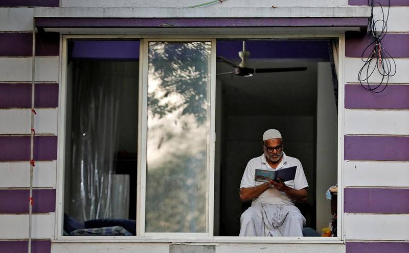 A man reads the Koran by the window of his house during the Muslim fasting month of Ramadan, during a nationwide lockdown to slow the spread of the coronavirus disease (COVID-19), in Ahmedabad, India, April 26, 2020. REUTERS/Amit Dave