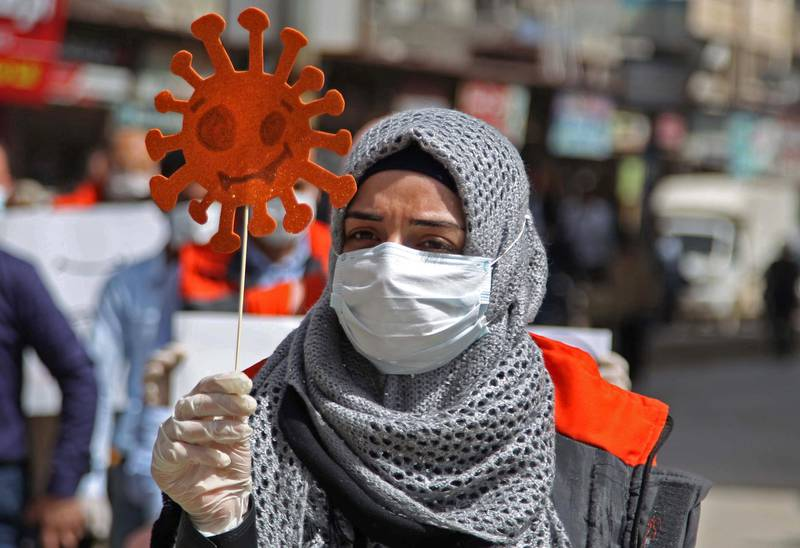 A mask-clad civil society volunteer marches with an effigy depicting the SARS-CoV-2 virion, the agent responsible for the COVID-19 coronavirus disease, during an awareness campaign about the novel coronavirus pandemic, urging people to remain at home, in Syria's northwestern city of Idlib in Idlib province on March 24, 2020. (Photo by Abdulaziz KETAZ / AFP)