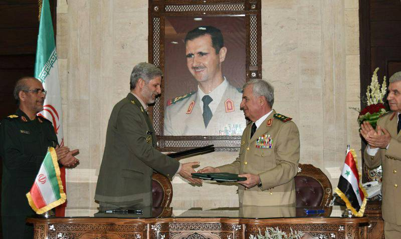 """A picture relased by the official Syrian Arab News Agency (SANA) on August 26, 2018 shows Iranian Defence Minister Amir Hatami (L) meeting with his Syrian counterpart Abdullah Ayoub (R) in the capital Damascus. Behind them is a portrait of Syrian president Bashar al-Assad. - Iran's top defence official met Syria's President Bashar al-Assad and its defence minister on today in Damascus, hailing their strong ties and pledging to contribute to the war-torn country's reconstruction. (Photo by Handout / SANA / AFP) / == RESTRICTED TO EDITORIAL USE - MANDATORY CREDIT """"AFP PHOTO / HO / SANA"""" - NO MARKETING NO ADVERTISING CAMPAIGNS - DISTRIBUTED AS A SERVICE TO CLIENTS =="""