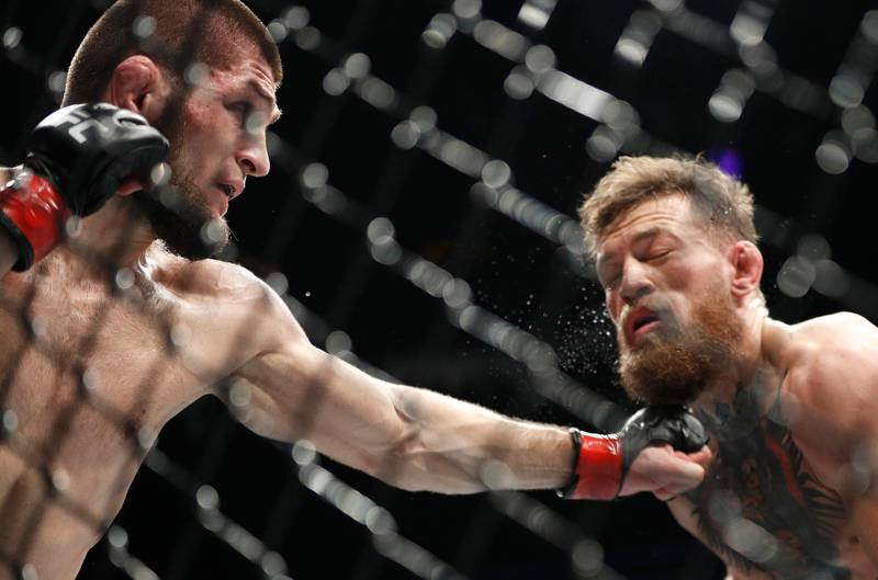 Khabib Nurmagomedov, left, punches Conor McGregor during a lightweight title mixed martial arts bout at UFC 229 in Las Vegas, Saturday, Oct. 6, 2018. (AP Photo/John Locher)