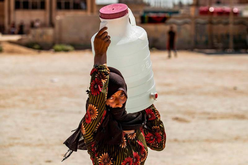 TOPSHOT - A displaced Syrian brings water back to their camp in a camp for the displaced in Syria's northeastern city of Hasakah on August 24, 2020.  / AFP / Delil SOULEIMAN