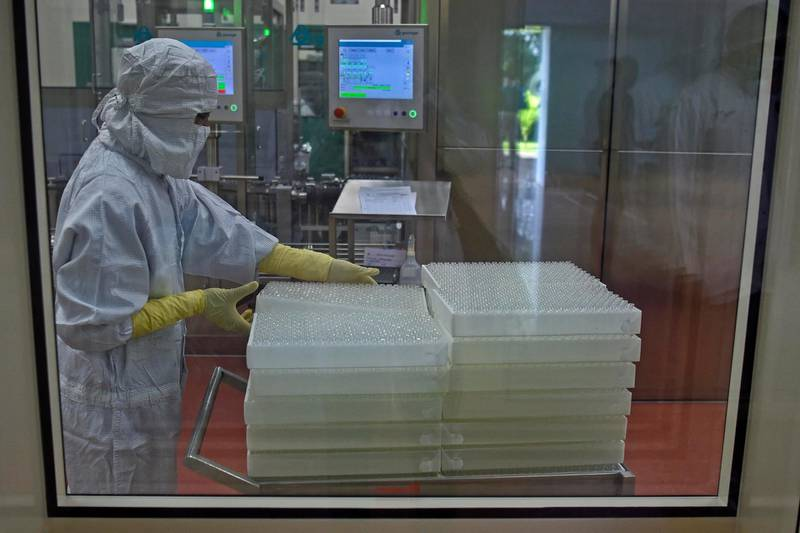 An employee in protective gear works on an assembly line for manufacturing vials of Covishield, AstraZeneca-Oxford's Covid-19 coronavirus vaccine at India's Serum Institute in Pune on January 22, 2021. (Photo by Punit PARANJPE / AFP)