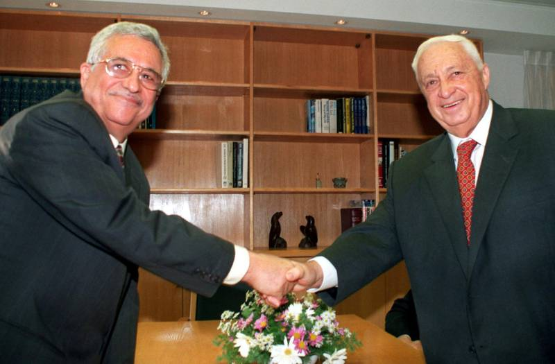 Mahmoud Abbas (L), the Palestinian negotiator better known as Abu Mazen, and Israeli Foreign Minister Ariel Sharon turn to the cameras and smile as they shake hands at the start of their meeting in Sharon's office November 18. The two met to review the work of all the Israeli-Palestinian peace committees and to set a date for the resumption of final status talks.  DPS/KM