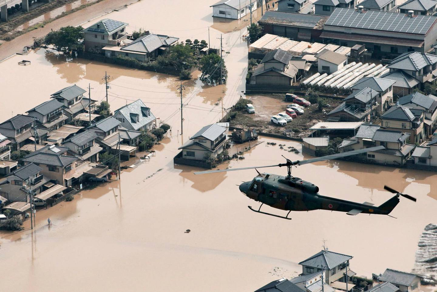 A helicopter flies over a flooded housing area in Kurashiki, Okayama prefecture, western Japan Monday, July 9, 2018. People prepared for risky search and cleanup efforts in southwestern Japan on Monday, where several days of heavy rainfall had set off flooding and landslides in a widespread area (Kyodo News via AP)