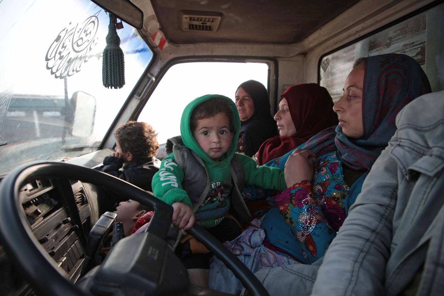 Syrians sit in a vehicle as they drive towards the northern areas of Syria's Idlib province near the Syrian-Turkish border as they flee the bombardments in the southern areas of the country's last major opposition bastion, on December 20, 2019. / AFP / Aaref WATAD