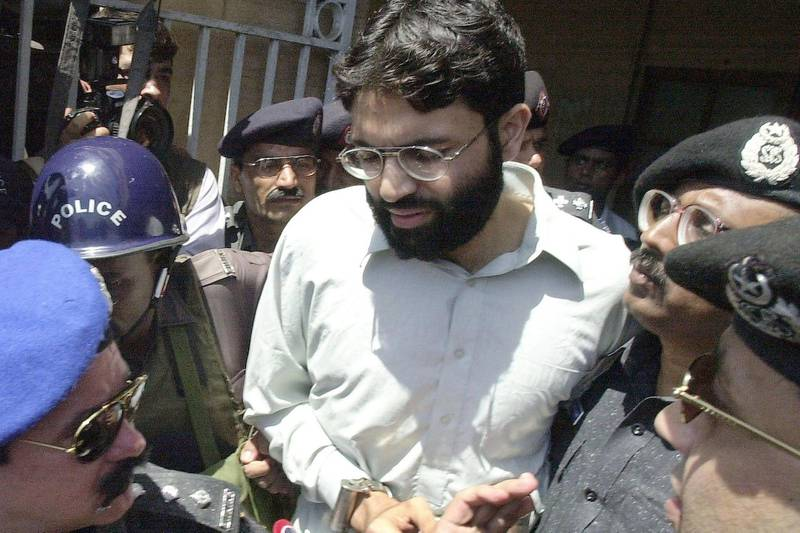 (FILES) In this file taken on March 29, 2002, Pakistani police surround handcuffed Omar Sheikh as he comes out of a court in Pakistan's port city of Karachi.  A Pakistani court on April 2, 2020 overturned the death sentence for British-born militant Ahmed Omar Saeed Sheikh, who had been convicted over the 2002 killing of American journalist Daniel Pearl.  / AFP / Aamir QURESHI