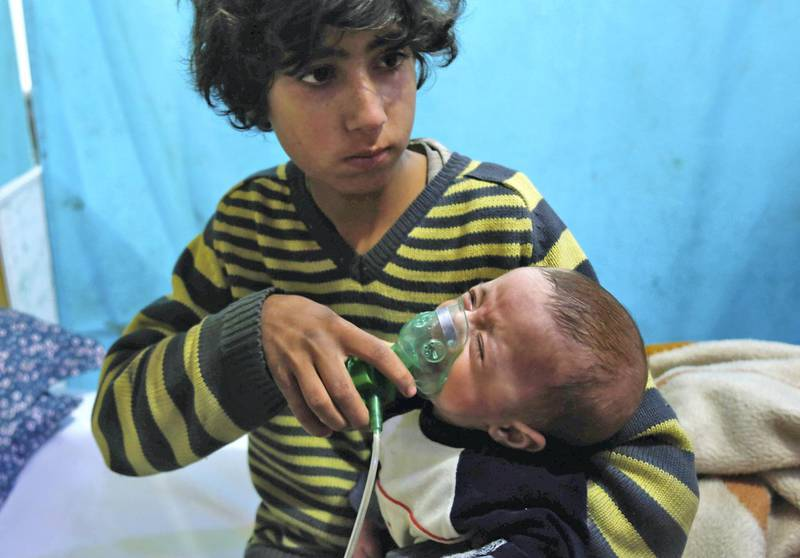 A Syrian boy holds an oxygen mask over the face of an infant at a make-shift hospital following a reported gas attack on the rebel-held besieged town of Douma in the eastern Ghouta region on the outskirts of the capital Damascus on January 22, 2018. - At least 21 cases of suffocation, including children, were reported in Syria in a town in eastern Ghouta, a beleaguered rebel enclave east of Damascus, an NGO accusing the regime of carrying out a new chemical attack said. Since the beginning of the war in Syria in 2011, the government of Bashar al-Assad has been repeatedly accused by UN investigators of using chlorine gas or sarin gas in sometimes lethal chemical attacks. (Photo by HASAN MOHAMED / AFP)