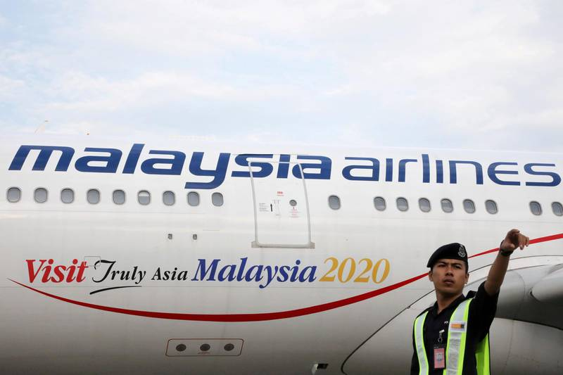 An airport employee beside a Malaysia Airlines plane at Kuala Lumpur International Airport in Sepang, Malaysia, July 22, 2019. REUTERS/Lim Huey Teng