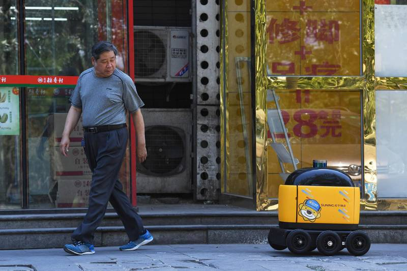 """A man looks back at a Zhen Robotics delivery robot as it makes its way back to a supermarket after making a delivery during a demonstration in Beijing. Along a quiet residential street on the outer edges of Beijing, a yellow and black cube about the size of a small washing machine trundles leisurely to its destination. This """"little yellow horse"""" is an autonomous delivery robot, ferrying daily essentials like drinks, fruit and snacks from the local store to the residents of the """"Kafka"""" compound in the Chinese capital.  - TO GO WITH AFP STORY CHINA-TECHNOLOGY-ROBOTS-CONSUMER-SCIENCE,FEATURE BY LUDOVIC EHRET  / AFP / GREG BAKER / TO GO WITH AFP STORY CHINA-TECHNOLOGY-ROBOTS-CONSUMER-SCIENCE,FEATURE BY LUDOVIC EHRET"""