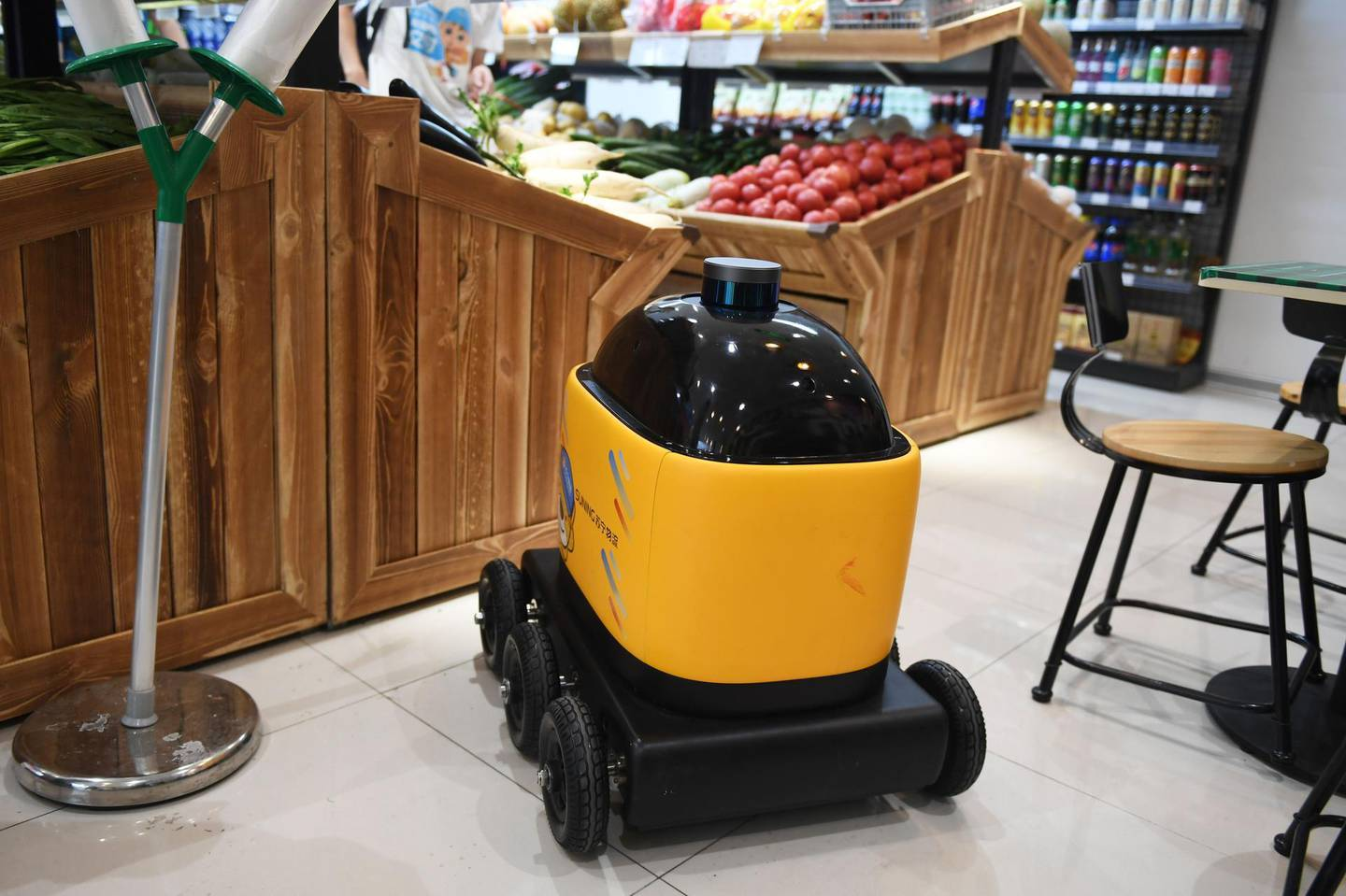 """In this photo taken on June 28, 2018, a Zhen Robotics delivery robot is seen in a Suning supermarket during a demonstration of the robot in Beijing. Along a quiet residential street on the outer edges of Beijing, a yellow and black cube about the size of a small washing machine trundles leisurely to its destination. This """"little yellow horse"""" is an autonomous delivery robot, ferrying daily essentials like drinks, fruit and snacks from the local store to the residents of the """"Kafka"""" compound in the Chinese capital.  - TO GO WITH AFP STORY CHINA-TECHNOLOGY-ROBOTS-CONSUMER-SCIENCE,FEATURE BY LUDOVIC EHRET  / AFP / GREG BAKER / TO GO WITH AFP STORY CHINA-TECHNOLOGY-ROBOTS-CONSUMER-SCIENCE,FEATURE BY LUDOVIC EHRET"""