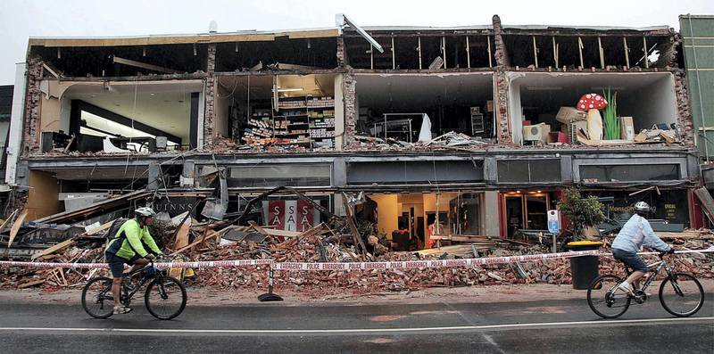 Cyclists riding past a damaged building in the Redcliffs suburb of Christchurch on February 23, 2011, a day after a deadly 6.3 magnitude earthquake rocked the city. AFP