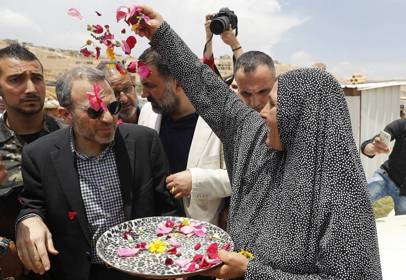 A Syrian refugee woman throws flowers on Lebanese Foreign Minister Gibran Bassil, center, during his visit a Syrian refugee camp, in Arsal, near the border with Syria, east Lebanon, Wednesday, June 13, 2018. A public spat between the Lebanese government and the United Nation's refugee agency deepened Wednesday as Lebanon's caretaker foreign minister kept up his criticism, accusing the agency of discouraging Syrian refugees from returning home. Lebanon is home to more than a million Syrian refugees, or about a quarter of the country's population, putting a huge strain on the economy. (AP Photo/Hussein Malla)