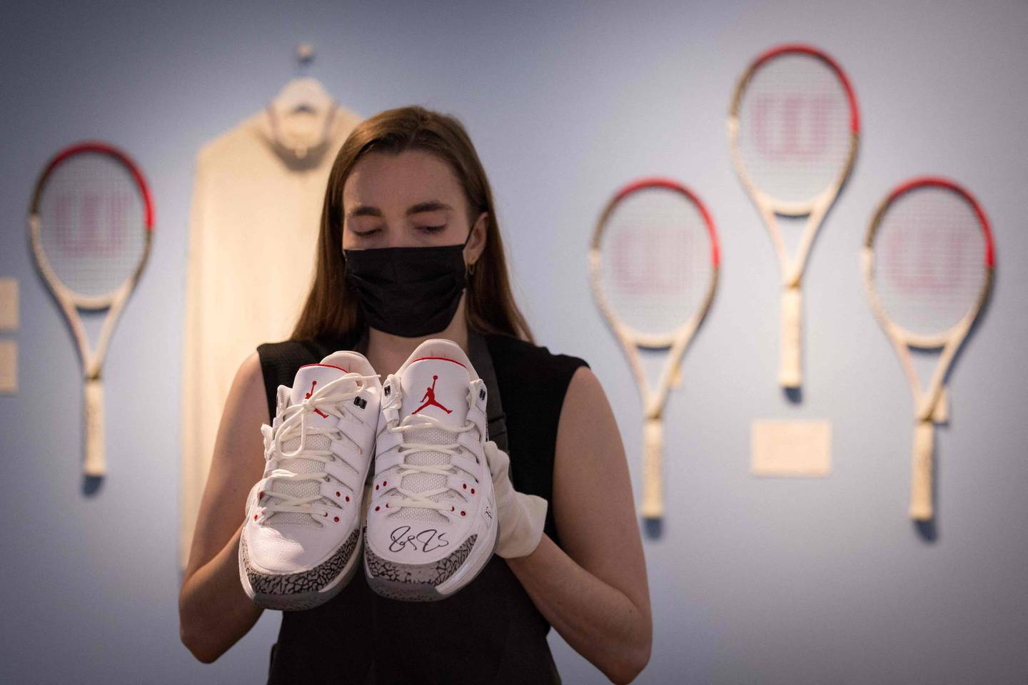An assistant poses with Swiss tennis champion Roger Federer's Nike Air Jordans from the 2014 US Open during a photocall at Christie's auction house in central London on June 21, 2021. / AFP / Tolga Akmen