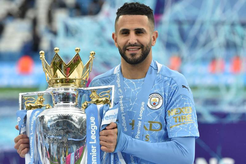 Manchester City's Algerian midfielder Riyad Mahrez holds the Premier League trophy during the award ceremony after the English Premier League football match between Manchester City and Everton at the Etihad Stadium in Manchester, north west England, on May 23, 2021. RESTRICTED TO EDITORIAL USE. No use with unauthorized audio, video, data, fixture lists, club/league logos or 'live' services. Online in-match use limited to 120 images. An additional 40 images may be used in extra time. No video emulation. Social media in-match use limited to 120 images. An additional 40 images may be used in extra time. No use in betting publications, games or single club/league/player publications.  / AFP / POOL / PETER POWELL                         / RESTRICTED TO EDITORIAL USE. No use with unauthorized audio, video, data, fixture lists, club/league logos or 'live' services. Online in-match use limited to 120 images. An additional 40 images may be used in extra time. No video emulation. Social media in-match use limited to 120 images. An additional 40 images may be used in extra time. No use in betting publications, games or single club/league/player publications.