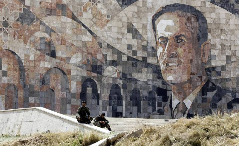 Syrian regime forces sit by a marble mosaic monument depicting a picture of late President Hafez al-Assad, at the entrance of Harasta in Eastern Ghouta on the outskirts of Damascus on March 25, 2018, after a deal was struck with rebels in the area to evacuate the town. (Photo by LOUAI BESHARA / AFP)