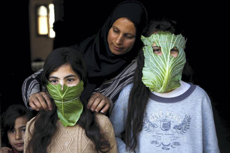 A Palestinian mother entertain her children with makeshift masks made of cabbage as she cooks in Beit Lahia in the northern Gaza Strip on April 16, 2020 amid the coronavirus COVID-19 pandemic. (Photo by MOHAMMED ABED / AFP)