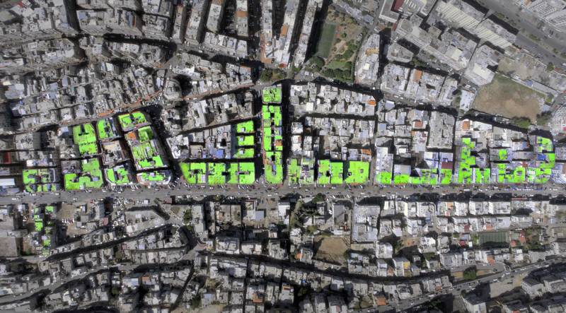 """A handout picture released by Ashekman on October 20, 2017, shows an aerial view of the word """"Peace"""" in arabic painted on the roofs of 85 buildings in Tripoli's Syria street which separetes the Sunni neighbourhood of Bab al-Tabbaneh from the Alawite neighbourhood of Jabal Mohsen. The project has been three years in the making, with the artists, 34-year-old twins Mohamed and Omar Kabbani, researching and rejecting multiple locations in their native Lebanon before settling on Tripoli. / AFP PHOTO / ASHEKMAN / Handout"""