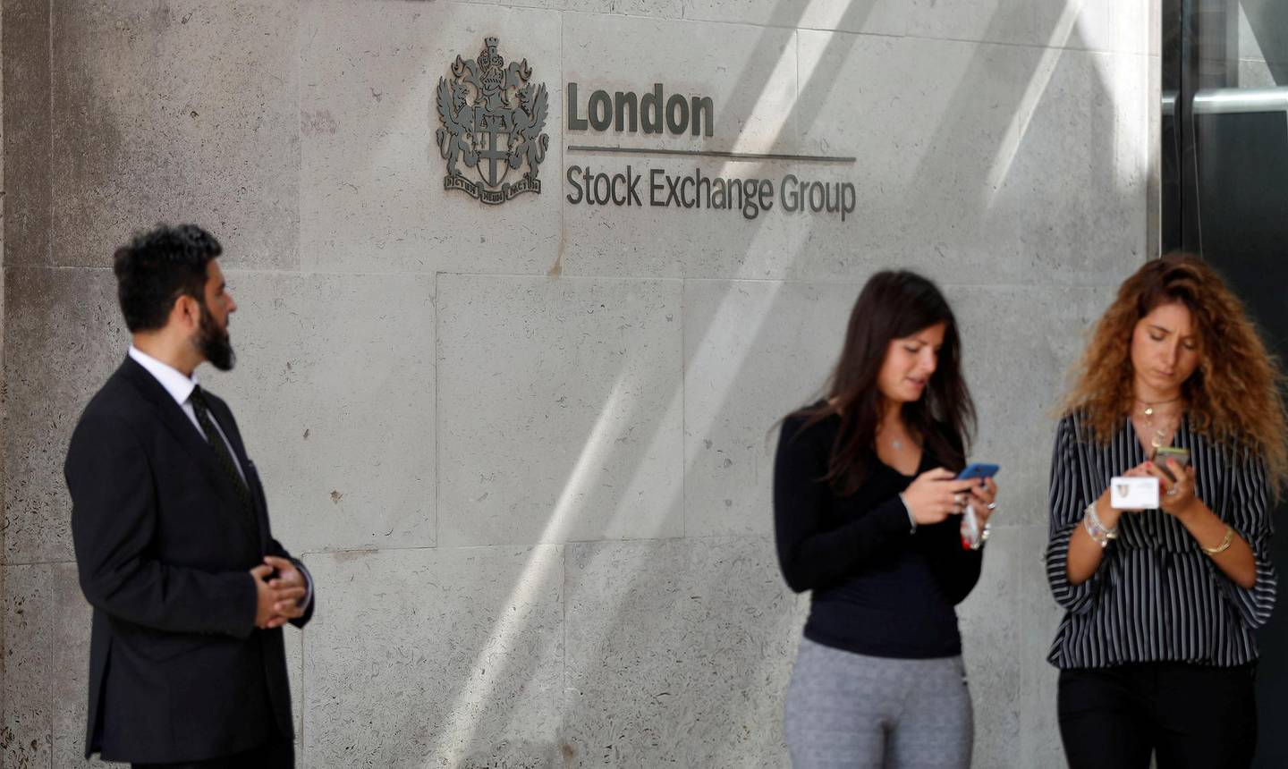FILE PHOTO: People check their mobile phones as they stand outside the entrance of the London Stock Exchange in London, Britain. Aug 23, 2018. REUTERS/Peter Nicholls/File Photo