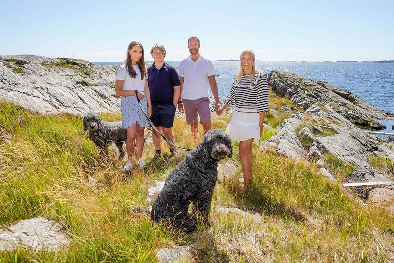 Norway's Crown Prince Haakon (2nd R), Crown Princess Mette-Marit (R), Prince Sverre Magnus (2nd L) and Princess Ingrid Alexandra (L) pose with their dogs  Milly Kakao (L) and Muffins Krakebolle (C) during their holiday on the island of Dvergsoya, near Kristiansand, on July 17, 2020. (Photo by Lise Åserud / NTB Scanpix / AFP) / Norway OUT