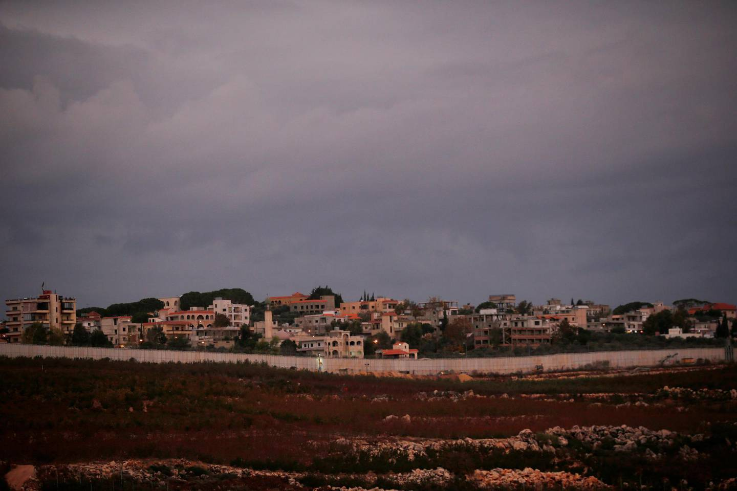 The Lebanese border village of Kfar Kila is seen behind the barrier wall as Israeli army personnel and heavy machinery work on the Israeli side of the border, in Israel's northernmost town Metula, early morning December 5, 2018.