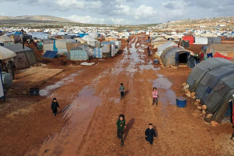Syrian refugees walk through a camp for displaced muddied by recent rains near the village of Kafr Aruq , in Idlib province, Syria, Thursday, Jan. 28, 2021. (AP Photo/Ghaith Alsayed)