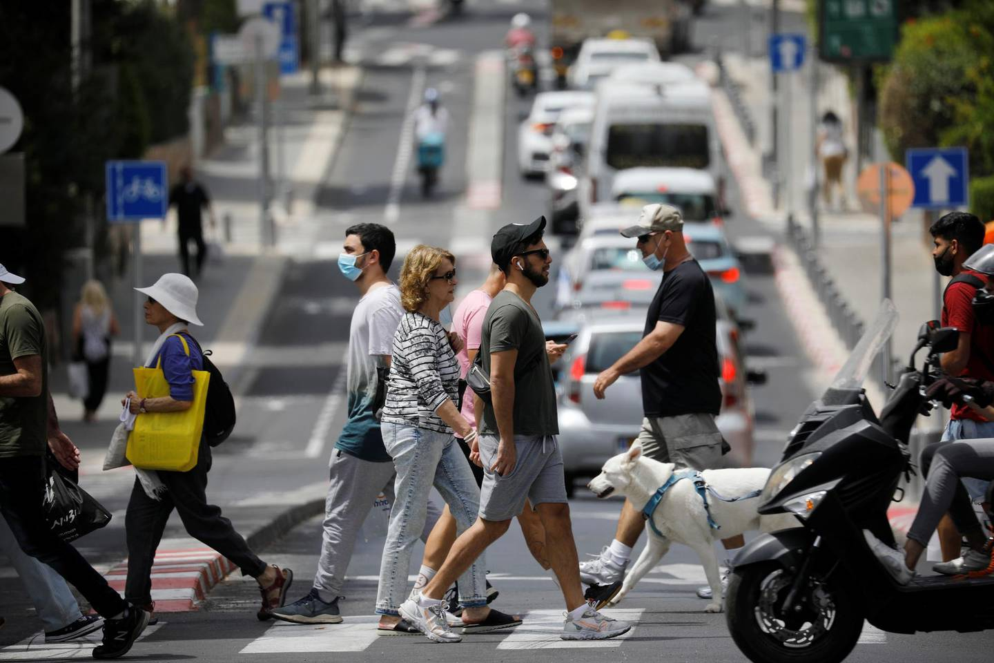 Pedestrians cross a street as Israel rescinds the mandatory wearing of face masks outdoors in the latest return to relative normality, boosted by a mass-vaccination campaign against the coronavirus disease (COVID-19) pandemic, in Tel Aviv, Israel April 18, 2021. REUTERS/Amir Cohen