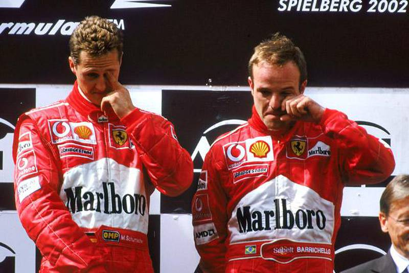 A1 RING - MAY 12:  Race winner Ferrari driver Michael Schumacher of Germany and runner-up Ferrari driver Rubens Barrichello of Brazil stand on the podium after the Austrian Formula One Grand Prix held at the A1 Ring in Spielberg, Austria on May 12, 2002. They swapped places on the podium as Barrichello led most of the race but under team orders let Schumacher overtake him on the last lap to win the race. (Photo by Tom Shaw/Getty Images)