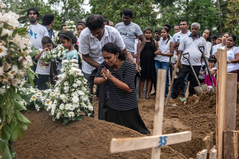 NEGOMBO, SRI LANKA - APRIL 25: A woman grieves at the grave after a funeral for a person killed in the Easter Sunday attack on St Sebastian's Church, on April 25, 2019 in Negombo, Sri Lanka. At least 359 people were killed and 500 people injured after coordinated attacks on churches and hotels on Easter Sunday which rocked three churches and three luxury hotels in and around Colombo as well as at Batticaloa in Sri Lanka. According to reports, police have identified eight out of nine attackers on Wednesday as the Islamic State group have claimed responsibility for the attacks. Police have detained 60 suspects so far in connection with the suicide bombs while the country's government blame the attacks on local Islamist group National Thowheed Jamath (NTJ). (Photo by Carl Court/Getty Images)