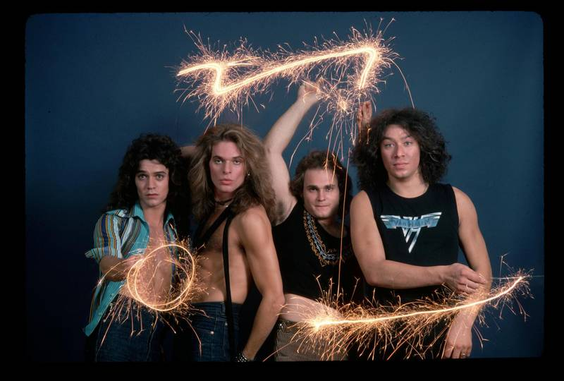 (Original Caption) : Picture shows the four members of the band Van Halen posing together in a studio. They are standing next to each other in front of a blue background waving sparklers in the air.   (Photo by Lynn Goldsmith/Corbis/VCG via Getty Images)
