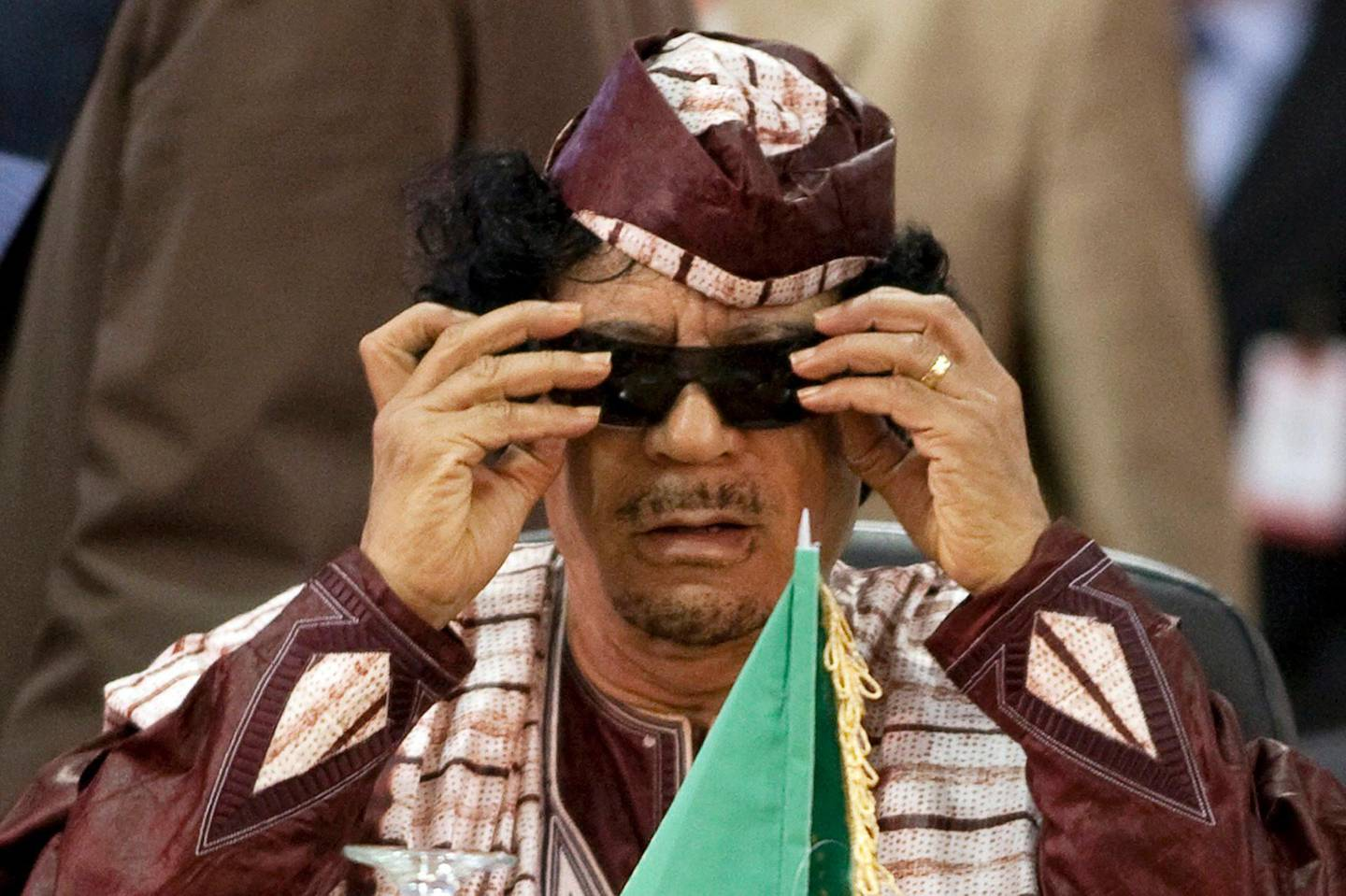 Libya's leader Muammar Gaddafi adjusts his glasses at the Africa-South America Summit on Margarita Island in this September 27, 2009 file photo. Gaddafi died of wounds suffered in his capture near his hometown of Sirte on October 20, 2011, a senior NTC military official said. National Transitional Council official Abdel Majid Mlegta told Reuters earlier that Gaddafi was captured and wounded in both legs at dawn on Thursday as he tried to flee in a convoy which NATO warplanes attacked.  REUTERS/Carlos Garcia Rawlins/Files (VENEZUELA - Tags: POLITICS) *** Local Caption ***  SIN303_LIBYA_1020_11.JPG