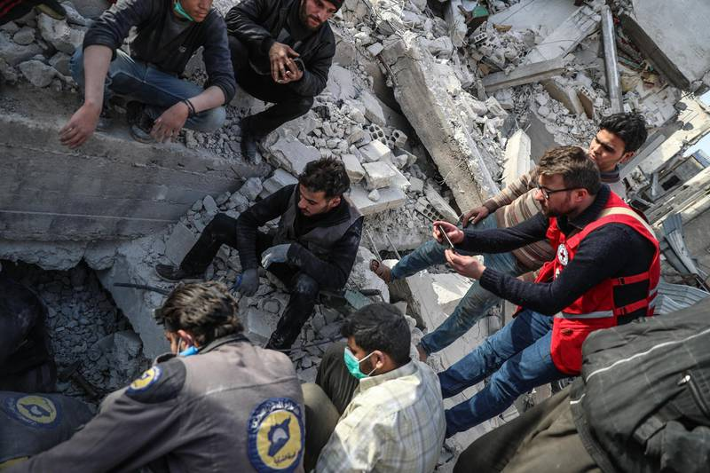 epa06584771 A volunteer with International Committee of the Red Cross photographs Civil defense rescuers searching for a body of victim under a collapsed building that was targeted by a strike on 22 February, after they were called to look for the victim buried under the rubbles in Douma, Syria, 05 March 2018 (issued 06 March 2018). Syrians in the neighborhood failed to reach the body of victim since the building collapsed on 22 February and on 05 March alerted the civil defense members to the possible place the body of the victim was trapped under the rubble as a convoy of the UN, Red Cross and Syrian Arab Red Crescent entered eastern Ghouta to deliver humanitarian aid.  EPA/MOHAMMED BADRA