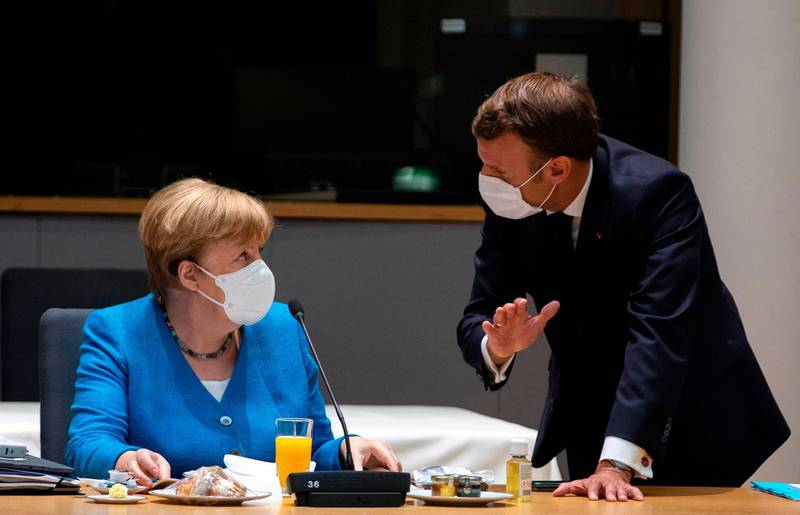 Germany's Chancellor Angela Merkel (L) talks with France's President Emmanuel Macron prior the start of the EU summit at the European Council building in Brussels, on July 18, 2020, as the leaders of the European Union hold their first face-to-face summit over a post-virus economic rescue plan. The EU has been plunged into a historic economic crunch by the coronavirus crisis, and EU officials have drawn up plans for a huge stimulus package to lead their countries out of lockdown.  / AFP / POOL / Francisco Seco