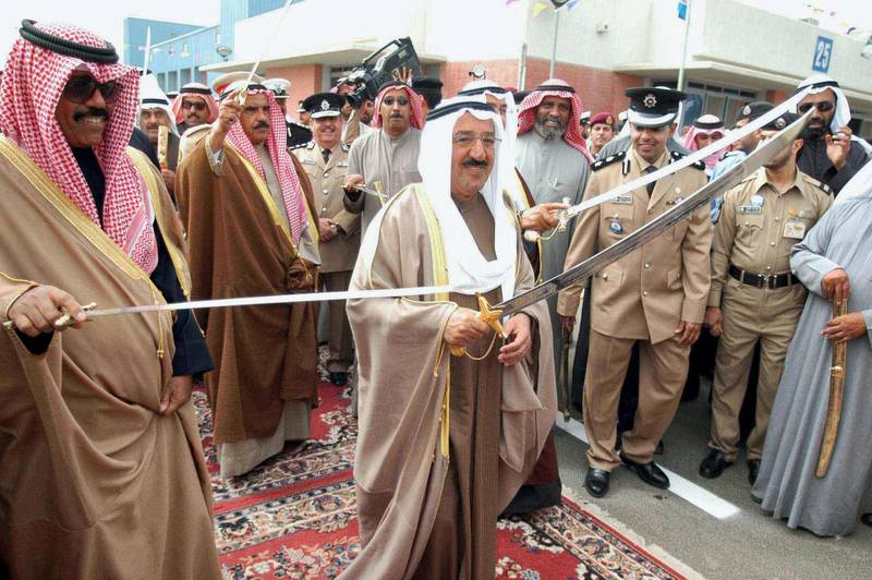 Kuwaiti Prime Minister Prince Sheikh Sabah al-Ahmad al-Sabah (C) dances a Kuwaiti traditional dance during the inauguration of the new Kuwaiti Sabah al-Ahmad al-Sabah naval base in Kuwait city 18 February 2004. The base is equipped with modern equipment and is considered one of the most modern bases in the Middle East, covering an area of 35,000 square meter.  AFP PHOTO/Yasser AL-ZYYAT (Photo by YASSER AL-ZAYYAT / AFP)