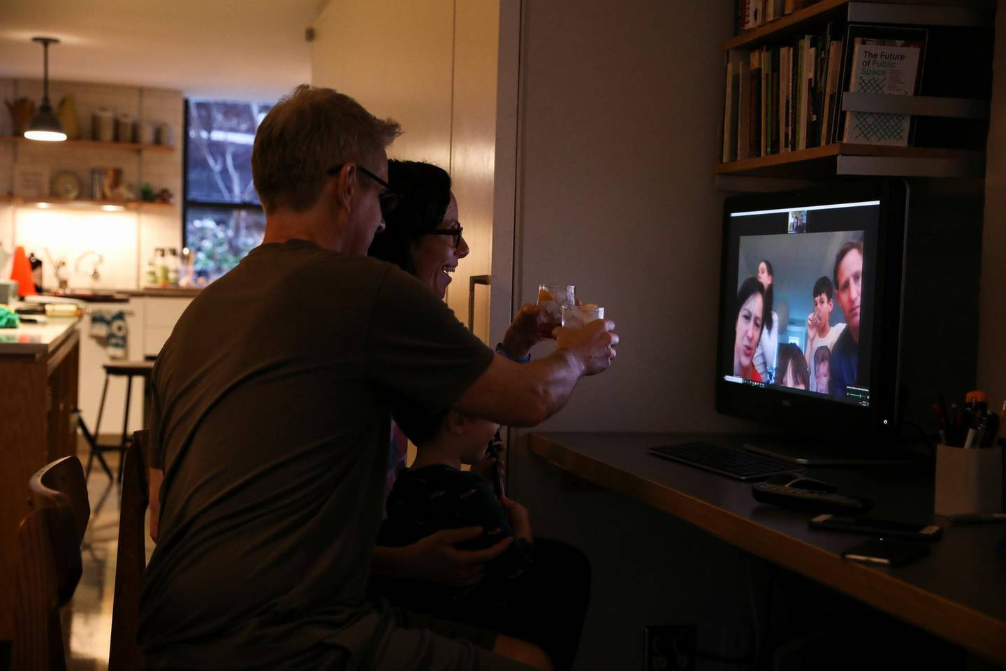 Naomi and her husband Doug Hassebroek enjoy a happy hour and cheers friends and family from their home using Zoom to connect digitally at the end of their first Friday working from home due to concerns over the rapid spread of coronavirus disease (COVID-19) in Brooklyn, New York, U.S., March 20, 2020. REUTERS/Caitlin Ochs