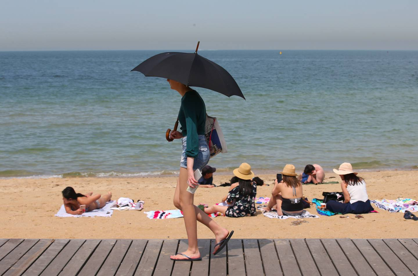 epa08078627 People flock to St Kilda beach as a heatwave sweeps across the state of Victoria, in St Kilda, south of Melbourne, Australia, 18 December 2019. According to media reports, a number of Australian states are bracing for rising temperatures that could exceed 40 degrees Celsius, as a heatwave continues across the country, increasing the risk of bushfires.  EPA/DAVID CROSLING  AUSTRALIA AND NEW ZEALAND OUT