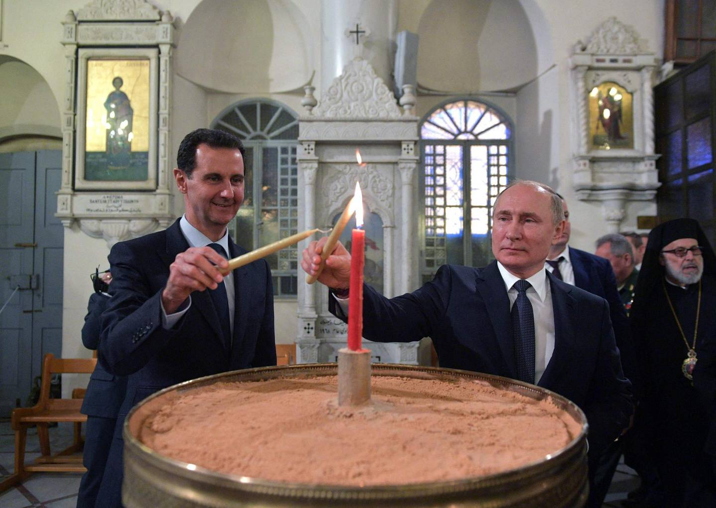 (FILES) In this file photo taken on January 07, 2020 Russian President Vladimir Putin and Syrian President Bashar al-Assad visit the Mariamite Cathedral of Damascus, one of the oldest Greek Orthodox churches in the Syrian capital, in Damascus. A decade of war may have ravaged his country, but Syria's President Bashar al-Assad has clung to power and looks determined to cement his position in presidential elections this year. / AFP / SPUTNIK / Alexey DRUZHININ