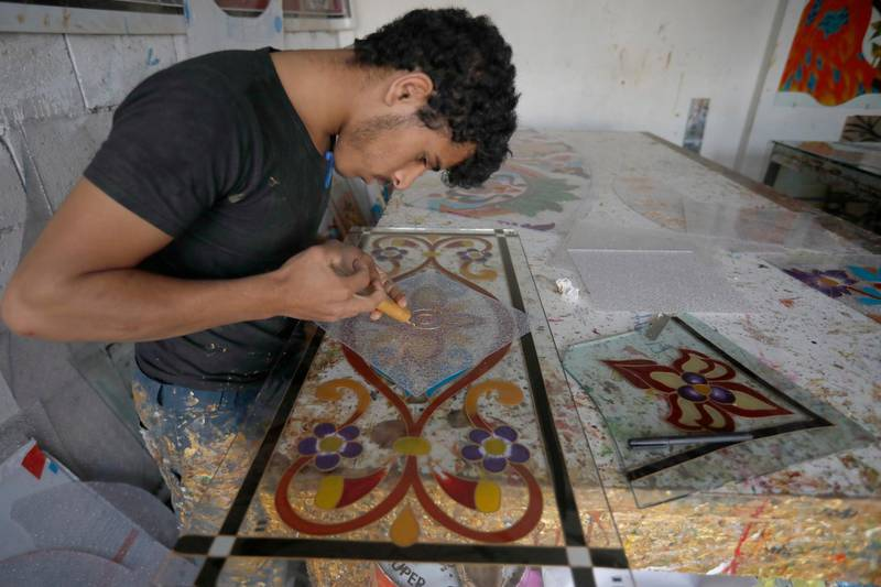 epa08566292 A Yemeni artist draws patterns on a plastic panel at a workshop in Sana'a, Yemen, 25 July 2020. Yemeni artists have started their own small businesses at a workshop in Sana'a to draw and paint patterns on plastic and glass panels as a way to improve the income in their war-ridden country.  EPA/YAHYA ARHAB